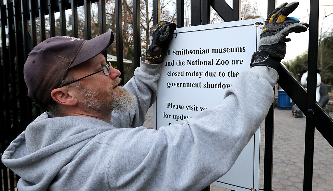 Man takes down a sign at the National Zoo