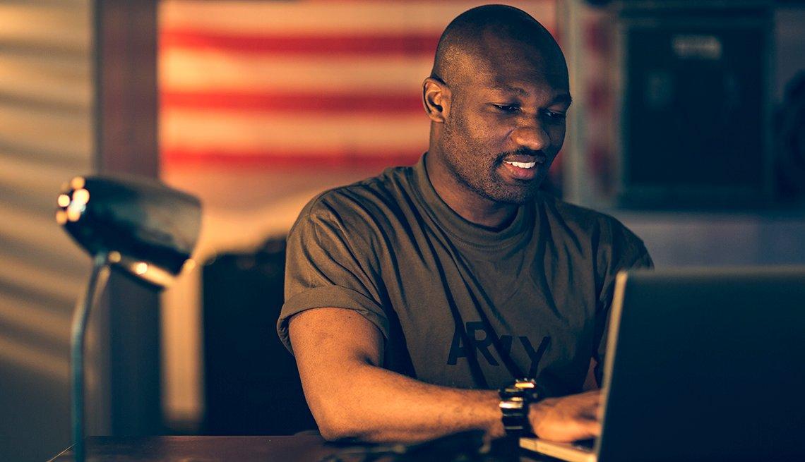Hombre con camisa del ejército frente a una computadora en una oficina.