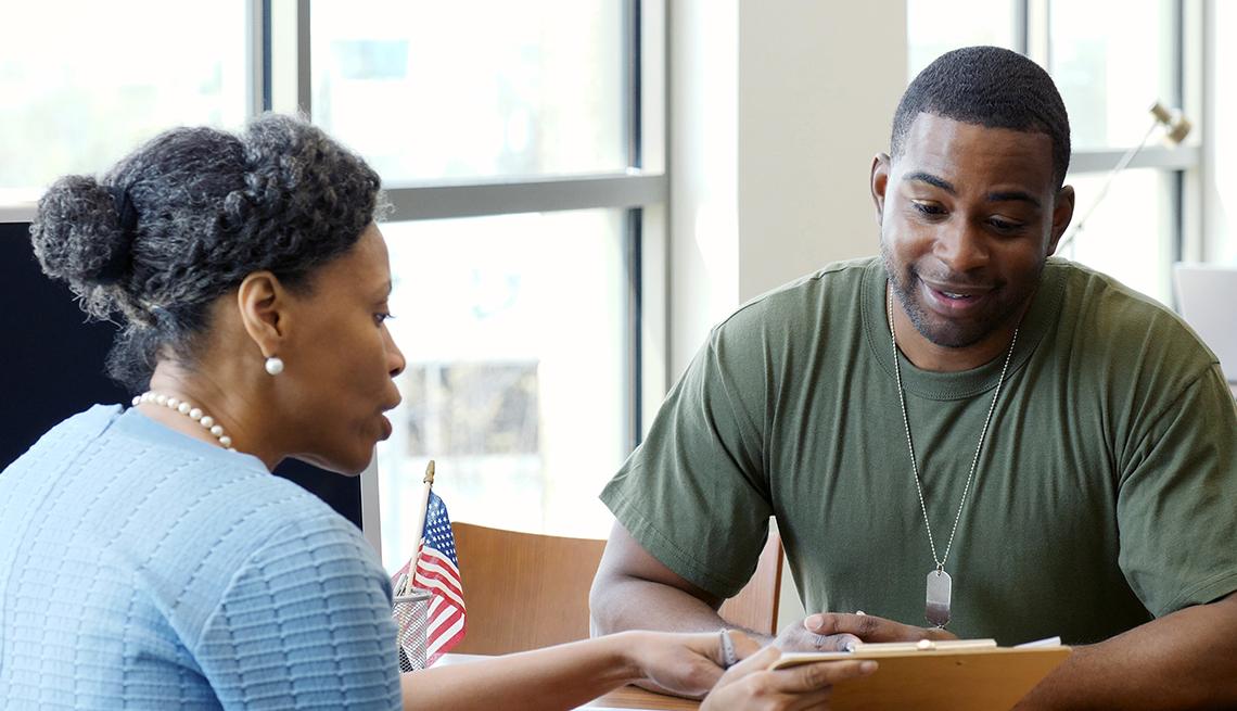Gerenta de banco discute opciones de cuenta de cheques y ahorro con un soldado