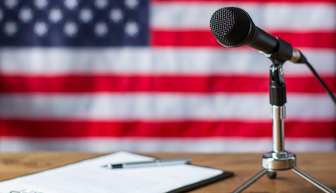Bandera de Estados Unidos, micrófono y portapapeles sobre la mesa
