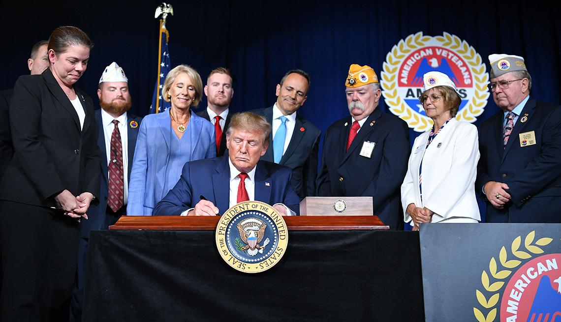 El presidente Donald Trump firma un documento en un escritorio con personas de pie detrás de él