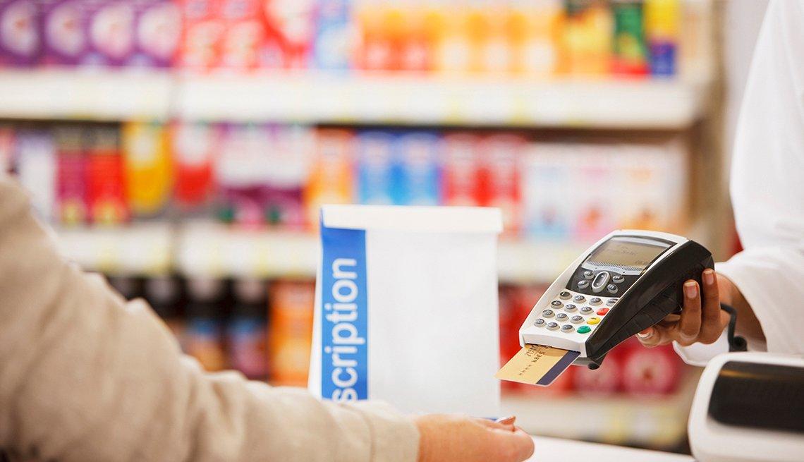 Una persona paga un medicamento con una tarjeta de crédito