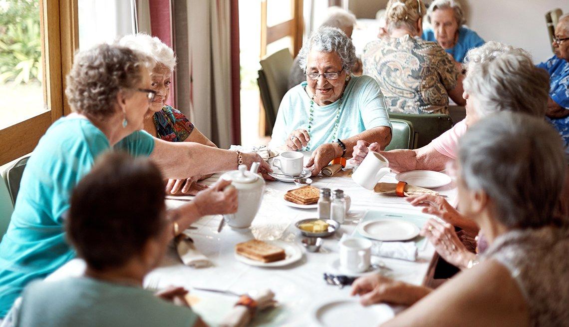 Grupo de mujeres mayores sentadas alrededor de una mesa desayunando