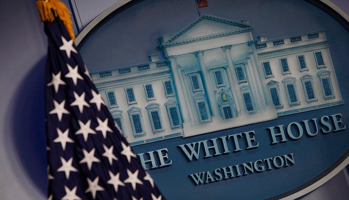 Imagen de la Casa Blanca junto a una bandera de Estados Unidos