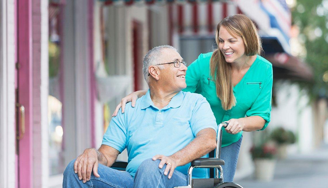 Mujer empuja a un hombre mayor sentado en una silla de ruedas