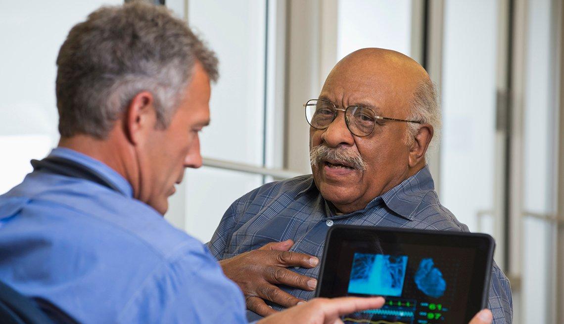 Un hombre mayor se agarra el pecho mientras habla con su médico