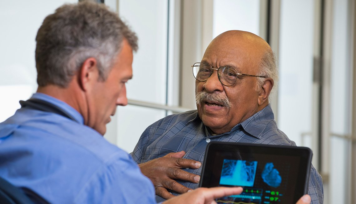 An older man is grabbing his chest while talking to his doctor