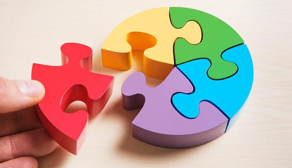 Un rompecabezas multicolor con una mano que agrega la última pieza