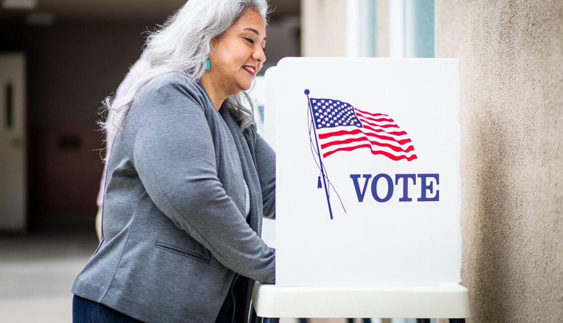 Mujer sonríe en una cabina de votación