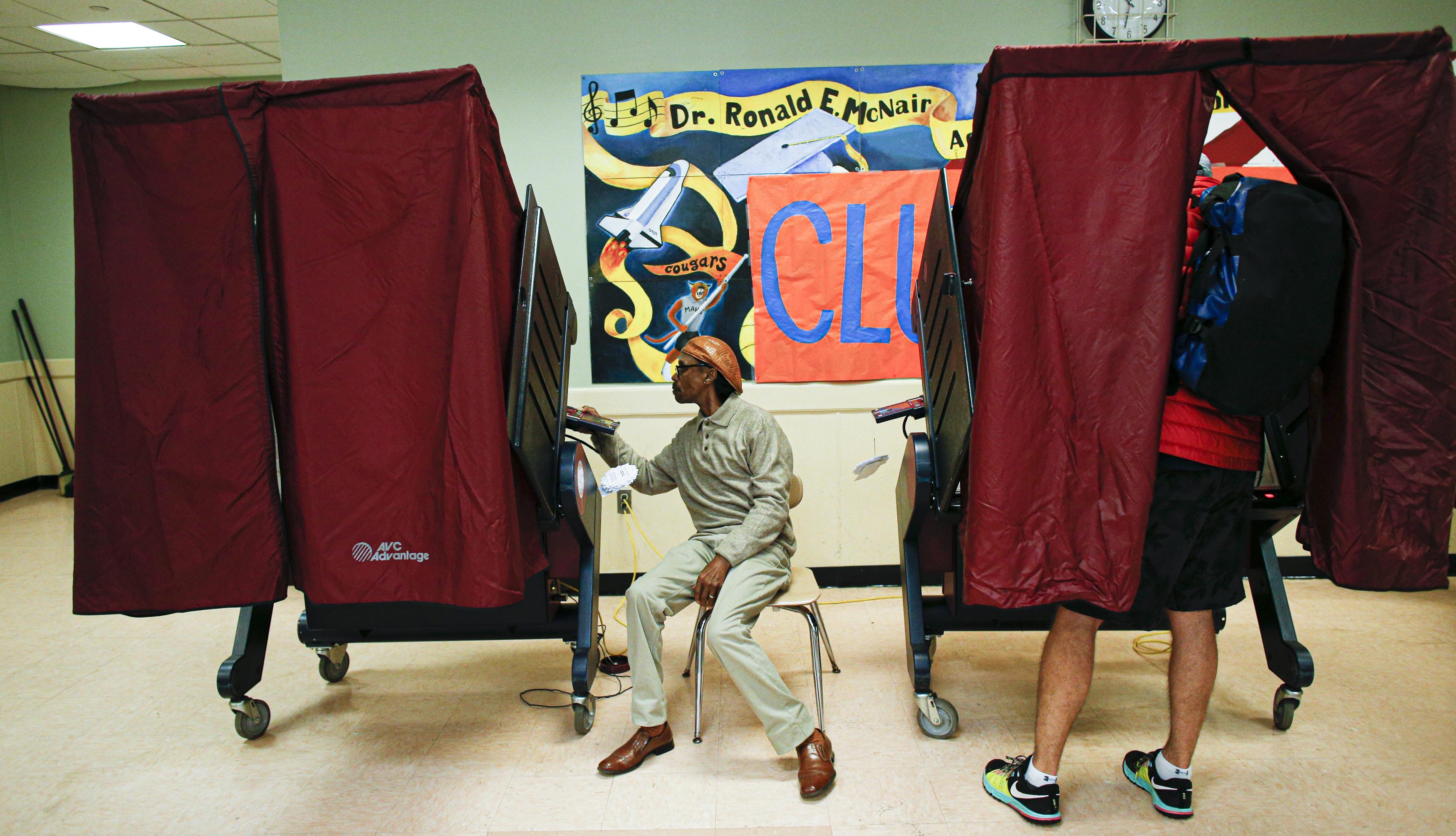 Un hombre vota en una mesa de votación con cortinas rojas en una escuela