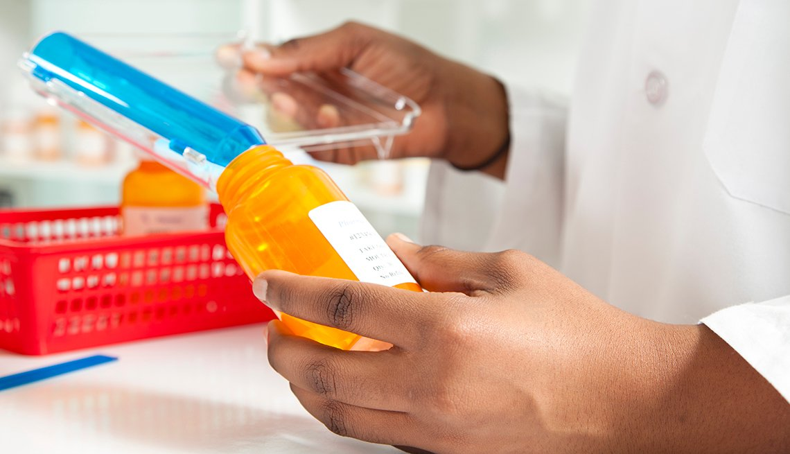A pharmacist is filling an orange prescription drug bottle