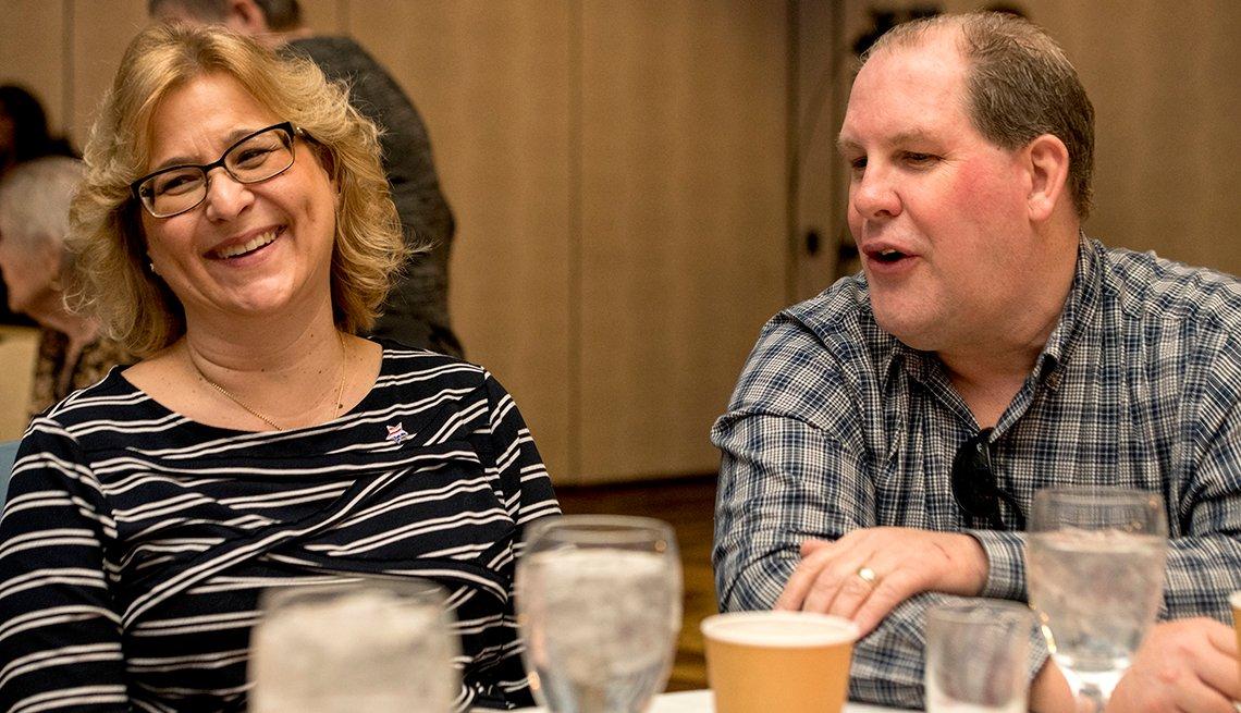 Un hombre y una mujer, sentados alrededor en una mesa, hablan durante un evento