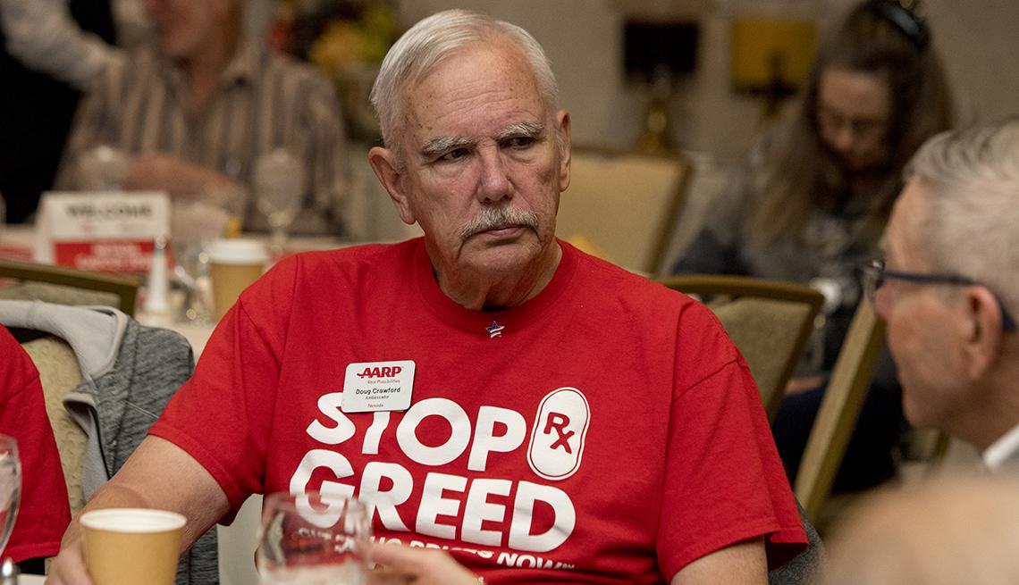 An older man wearing a red shirt at an event