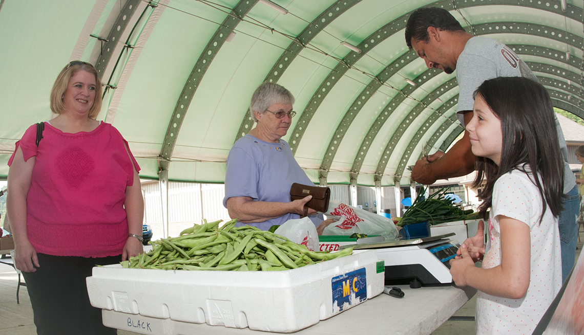 An older woman buys produce from a market
