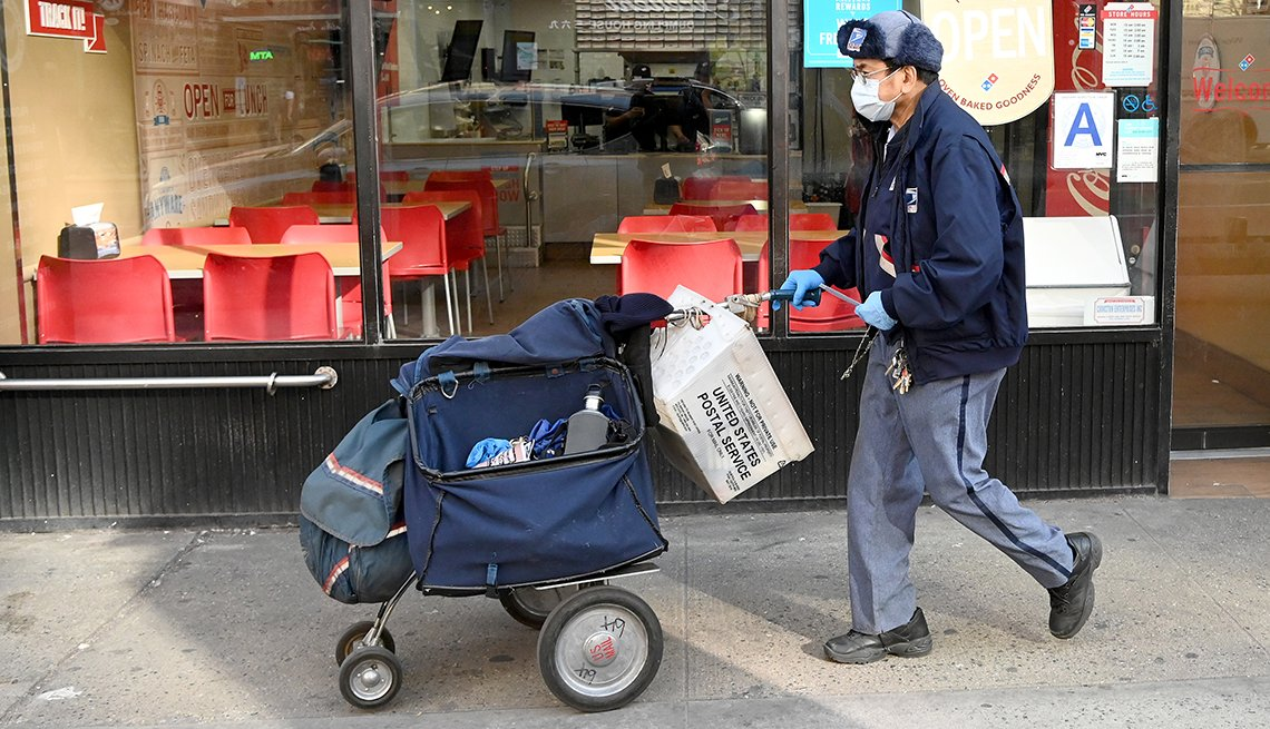 A mail carrier walking down the street with bags of mail