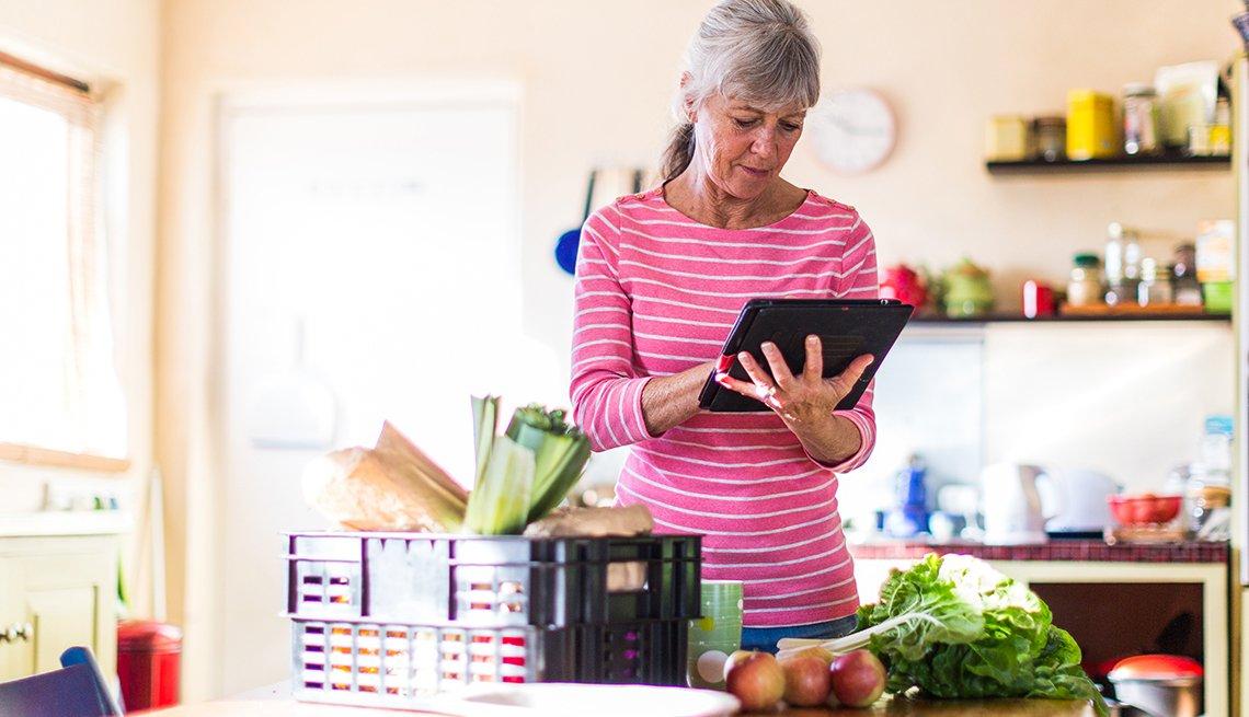 Una mujer mira su tableta parada en su cocina y alimentos sobre la mesa
