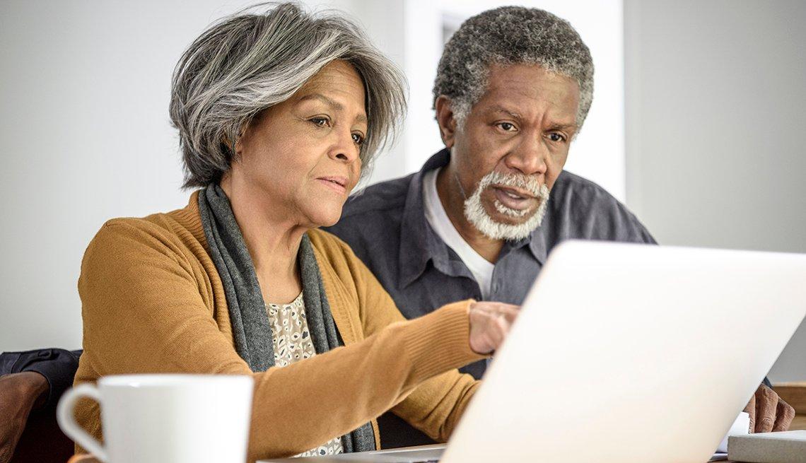 Pareja de adultos mayores viendo la pantalla de una computadora