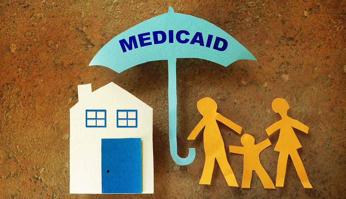 Figuras de papel de una familia frente a su casa, bajo un paraguas de Medicaid