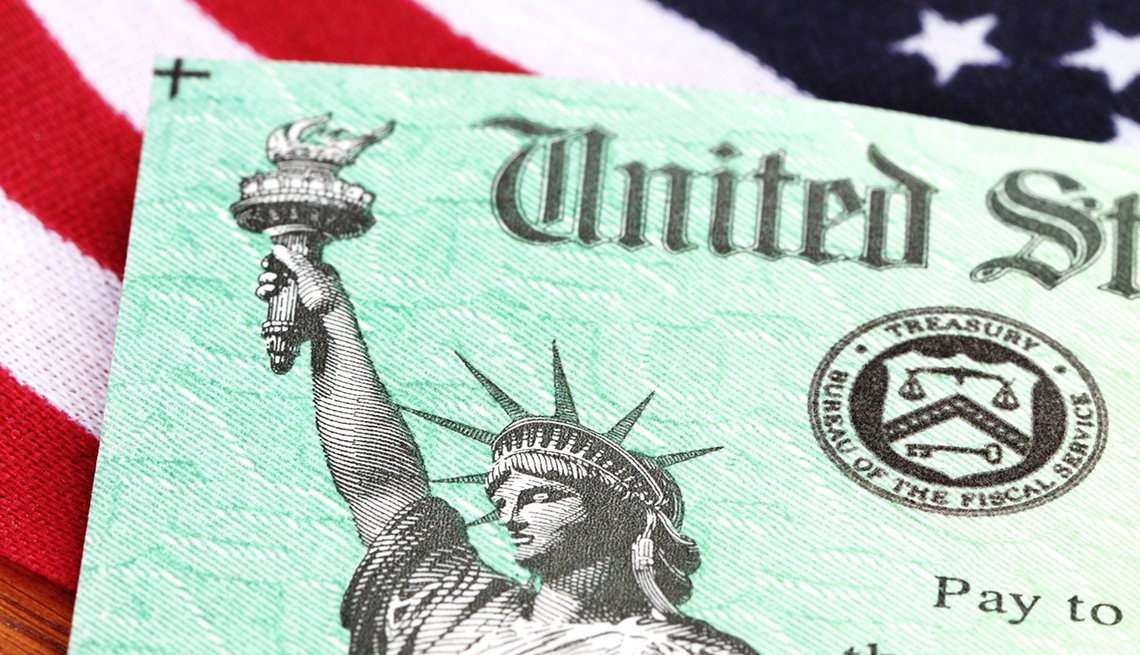 A check from the U S Treasury on an American Flag