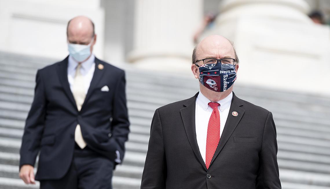 Two men walking up steps wearing masks