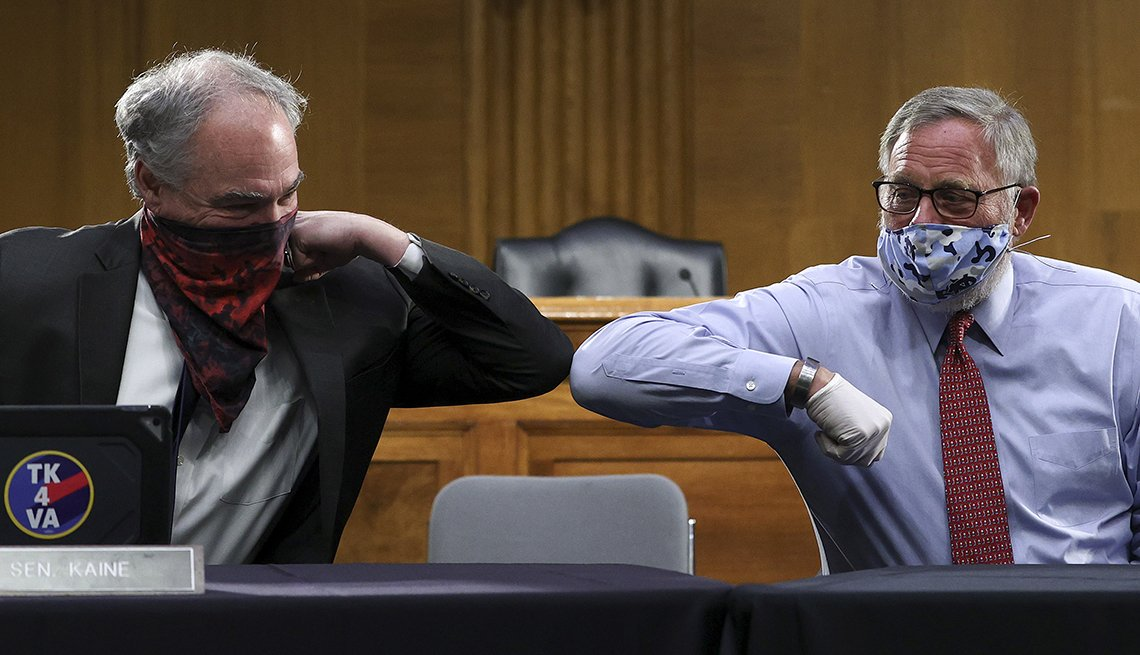 two senators bump elbows while wearing face masks at a hearing