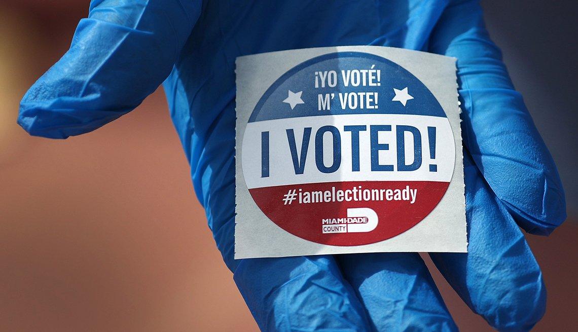 Mano con guante azul sostiene una calcomanía que dice, yo voté