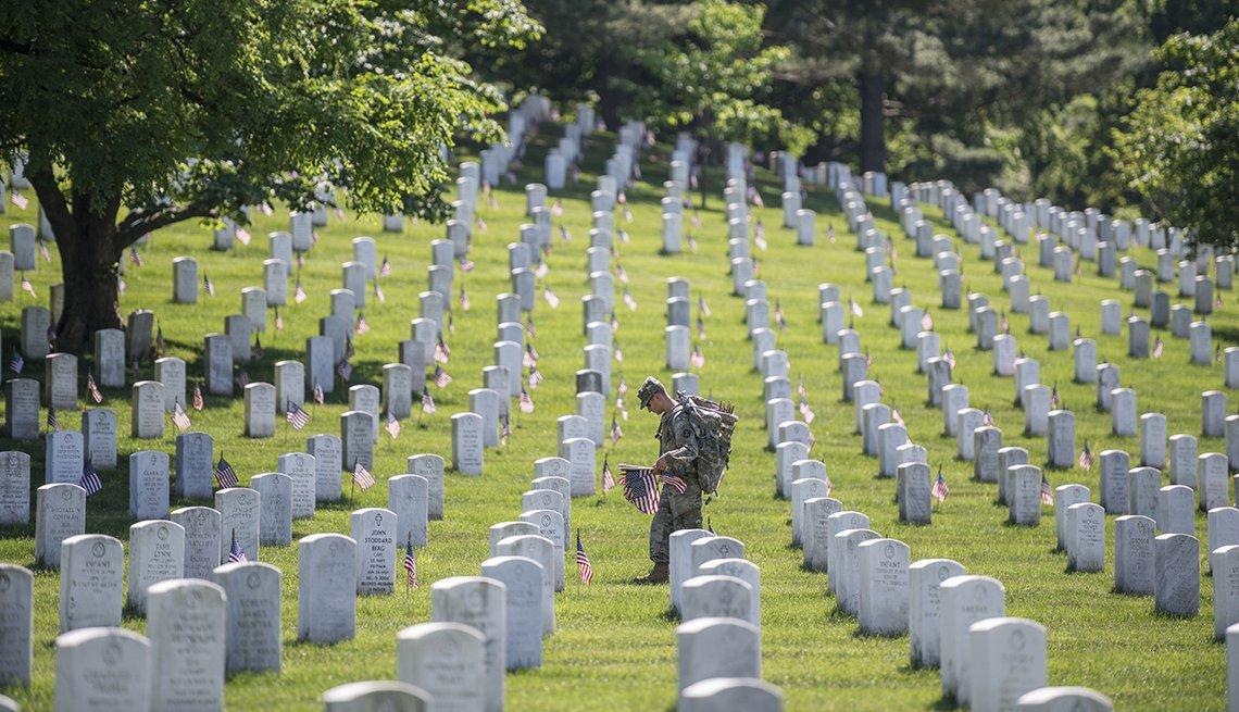 Un soldado pone banderas en las tumbas de un cementerio