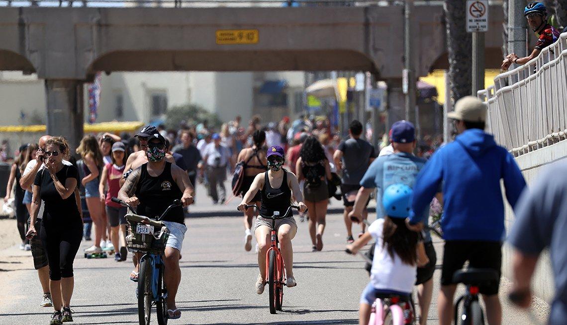 Gente caminando y montando bicicleta en la playa