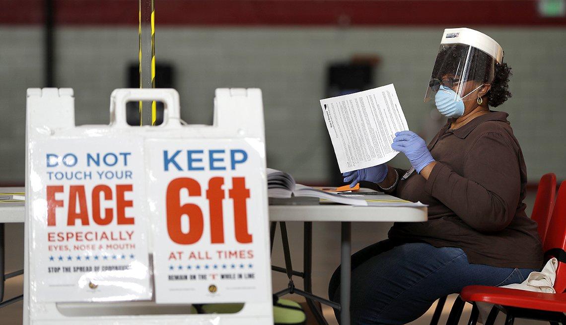 Mujer, protegida con una máscara, está sentada en un lugar de votación electoral
