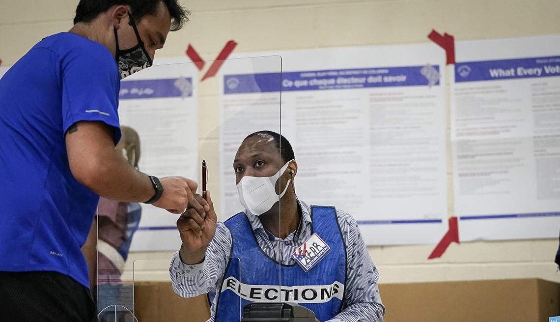 Dos hombres hablan en un puesto de votación electoral