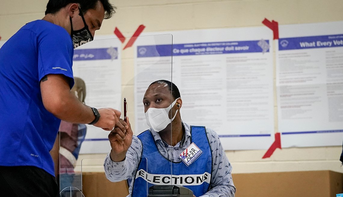 A person is talking to another person at a polling location during the election