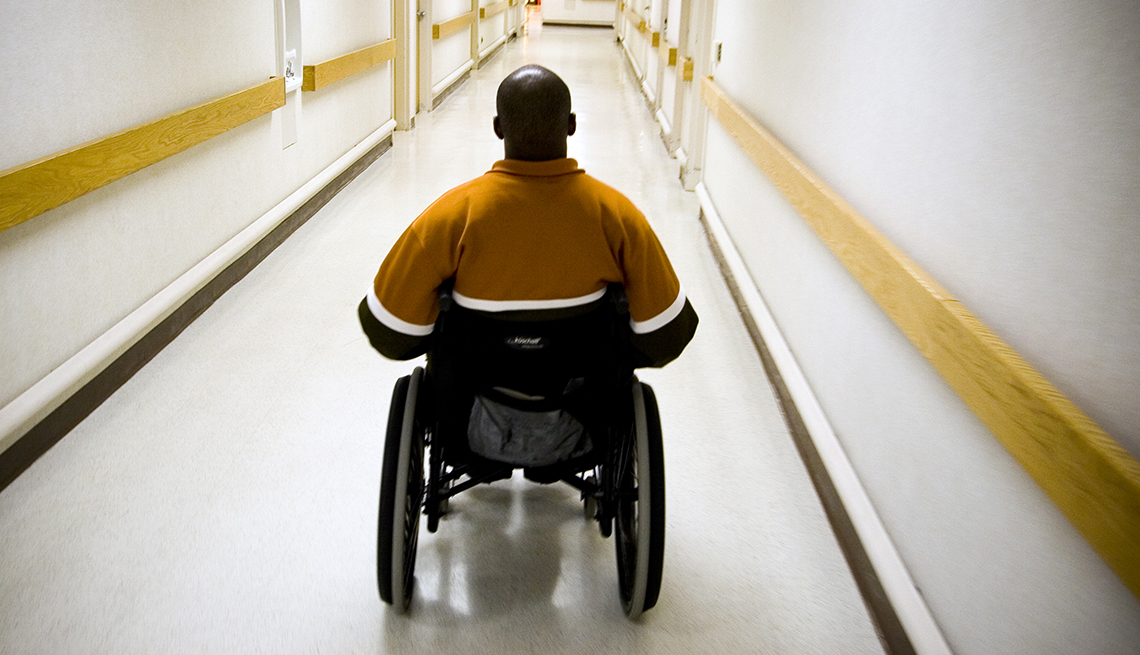 A man in a wheelchair goes down a hall way