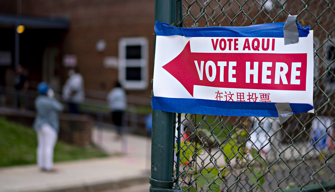A vote here sign is attached to a fence
