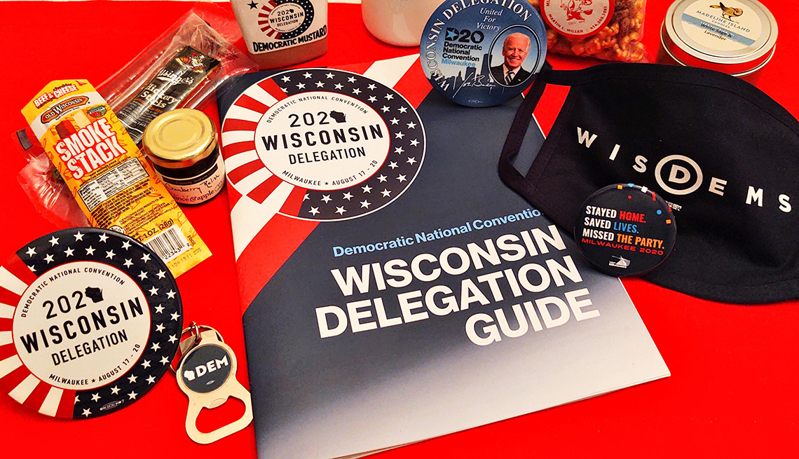 delegate swag from the twenty twenty democratic national convention in wisconsin features a face mask buttons bottle opener stickers and cheese
