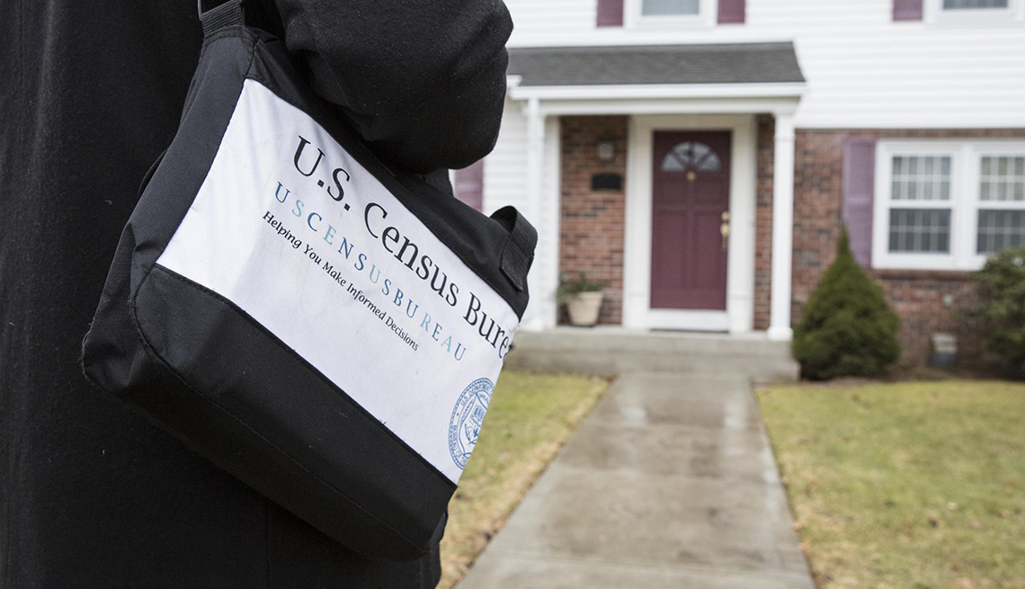 close up of a shoulder bag with census logo as worker approaches front door of home