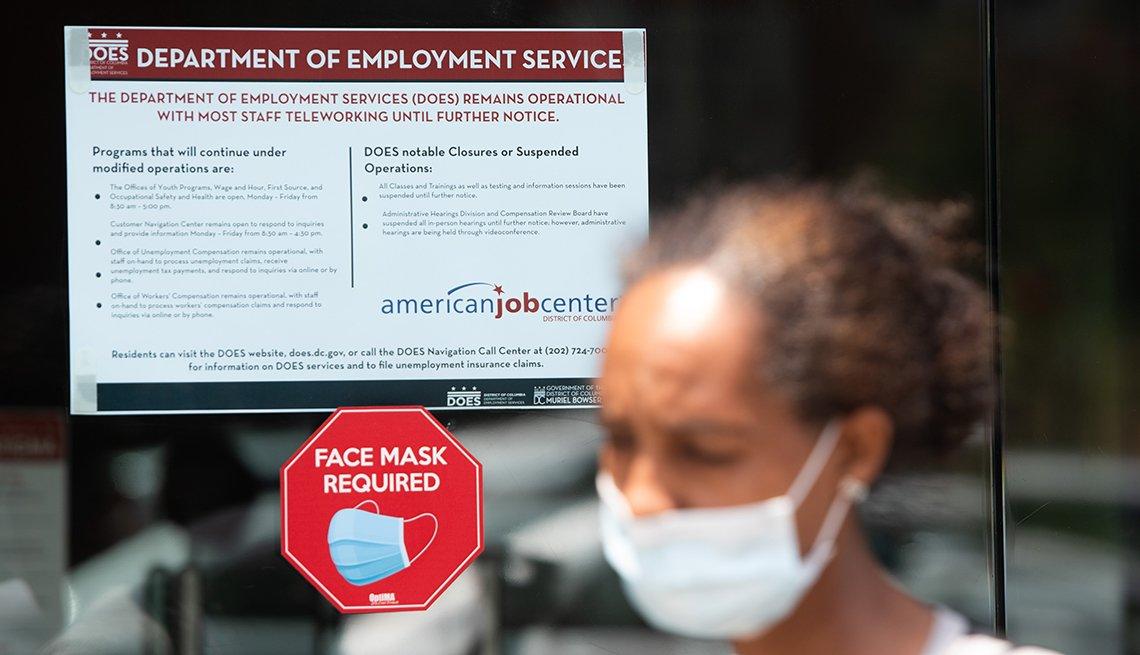 Una mujer sale de un edificio de servicios de empleo con una mascarilla puesta