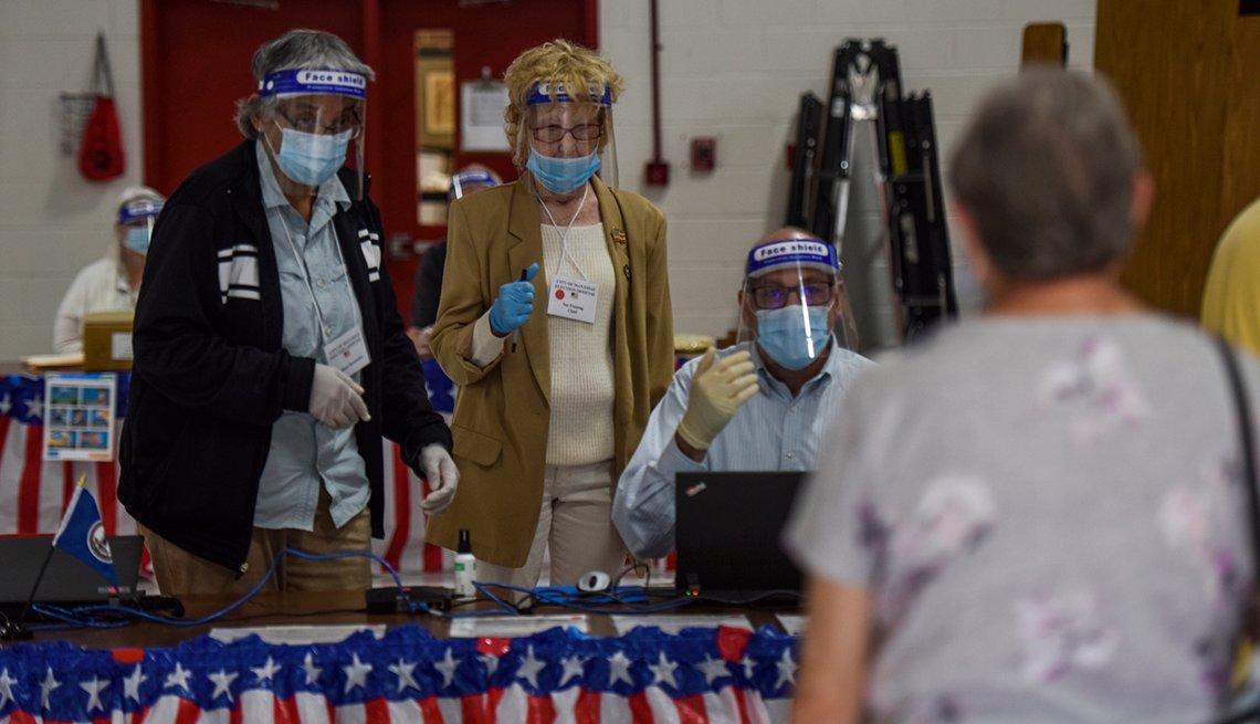 Personas, con mascarillas, esperan para votar en un centro electoral