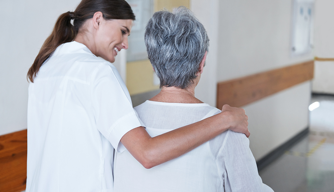 Una enfermera camina con su brazo sobre el hombro de otra mujer mayor