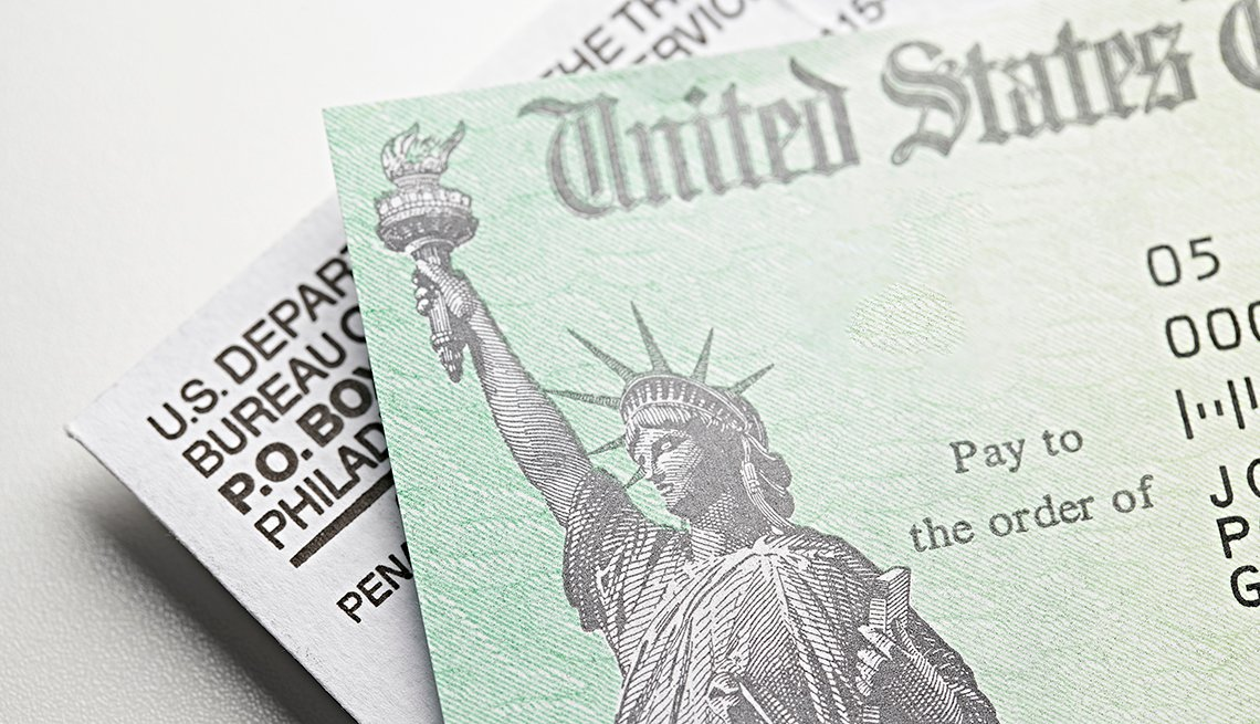 Un cheque de color verde junto a un sobre