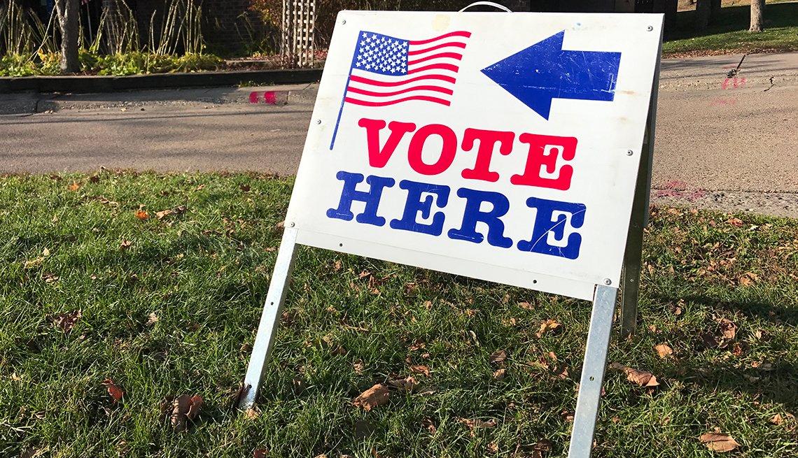 Letrero con una flecha en donde se puede leer en inglés VOTE HERE