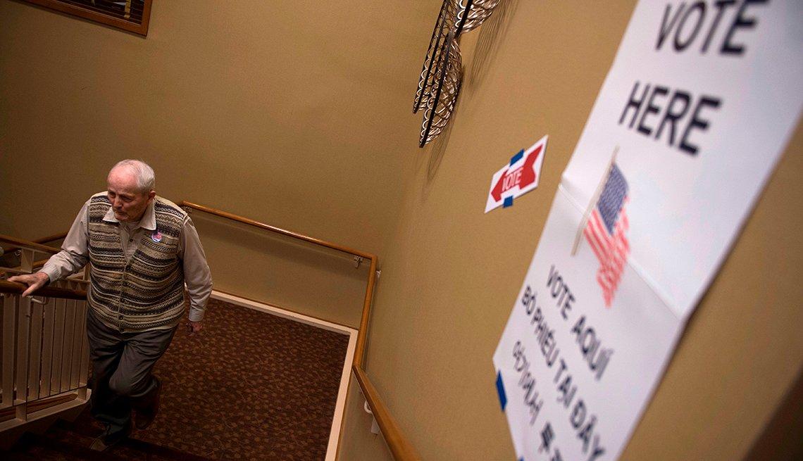 Un hombre mayor sube las escaleras a un lugar de votación