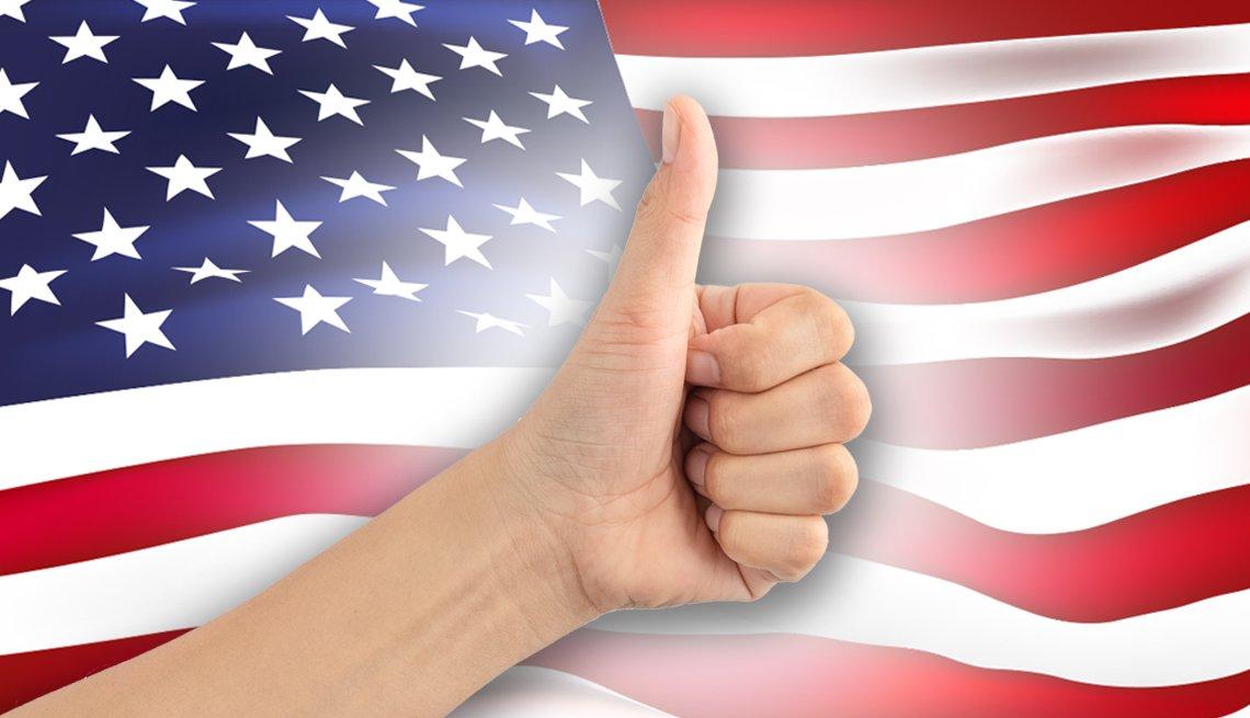 Mano con el dedo pulgar hacia arriba frente a una bandera estadounidense