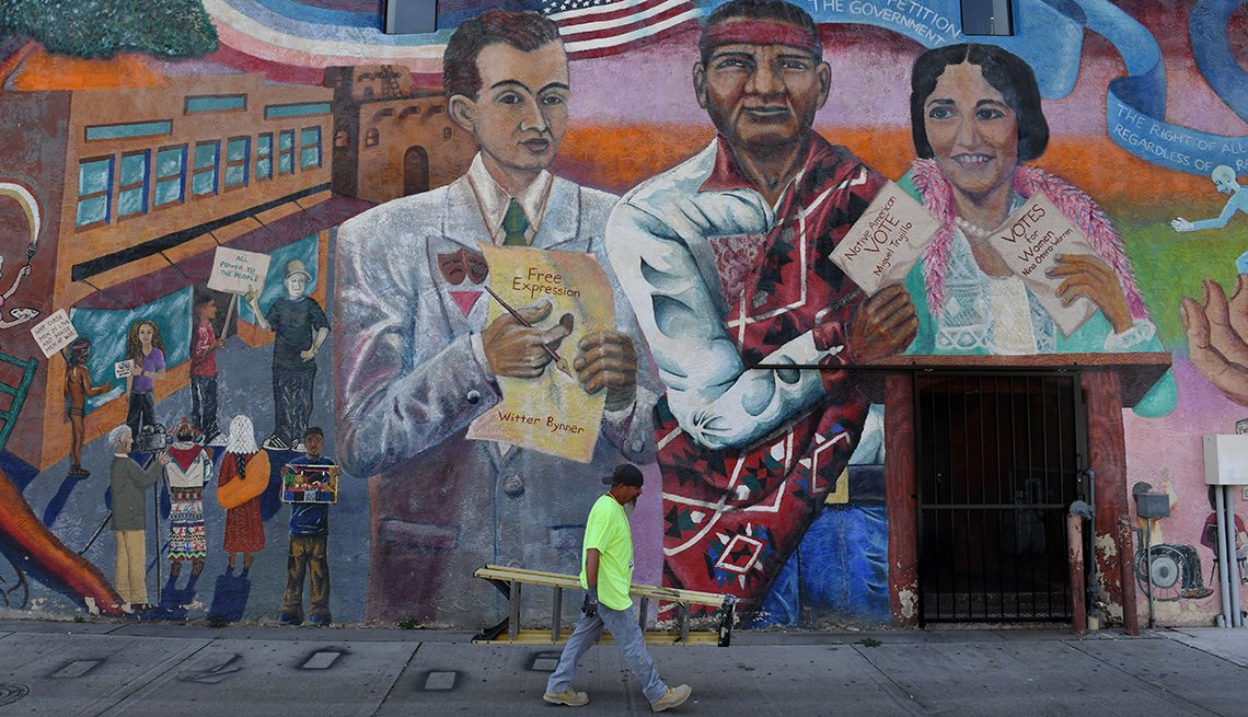 Un hombre pasa caminando junto a un mural en la pared de un edificio