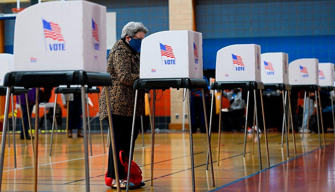 Mujer está votando en una cabina de votación durante las elecciones