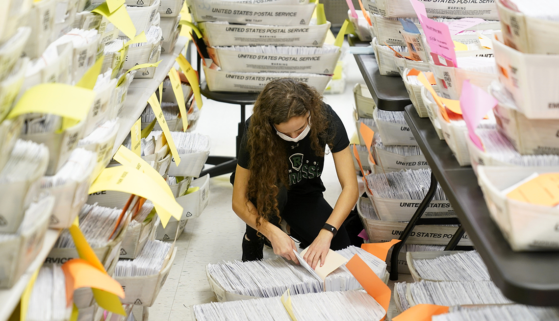 A woman sorts through hundreds of ballots