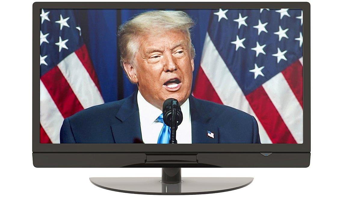 Imagen de Donald Trump en un monitor mientras habla en un discurso frente al micrófono