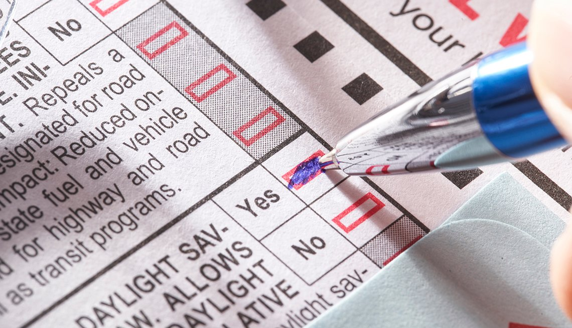 A person colors in a yes box on a ballot with a blue pen
