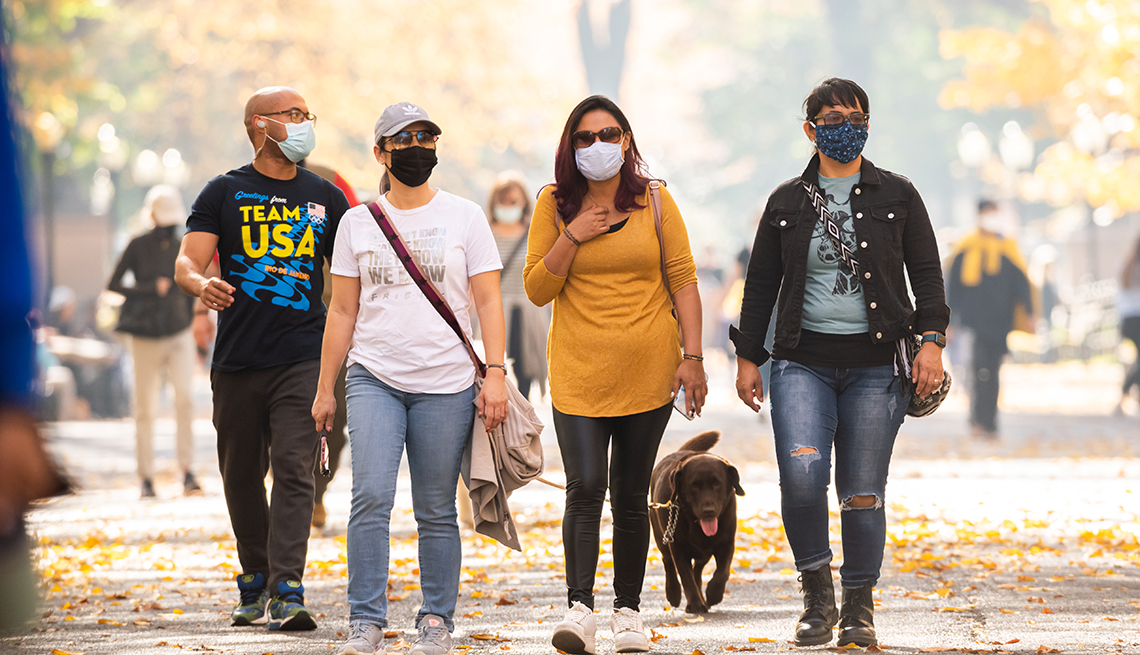Personas que usan máscara caminan por un parque durante la temporada de otoño