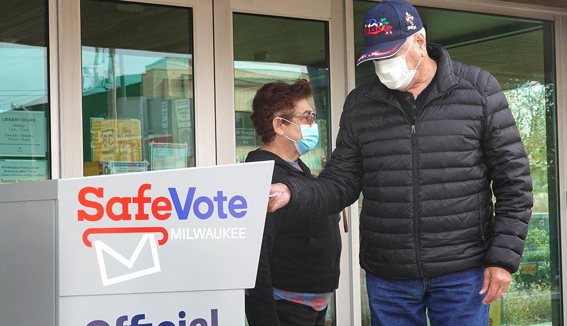 Un hombre, parado junto a una mujer, deposita su voto en un buzón electoral.