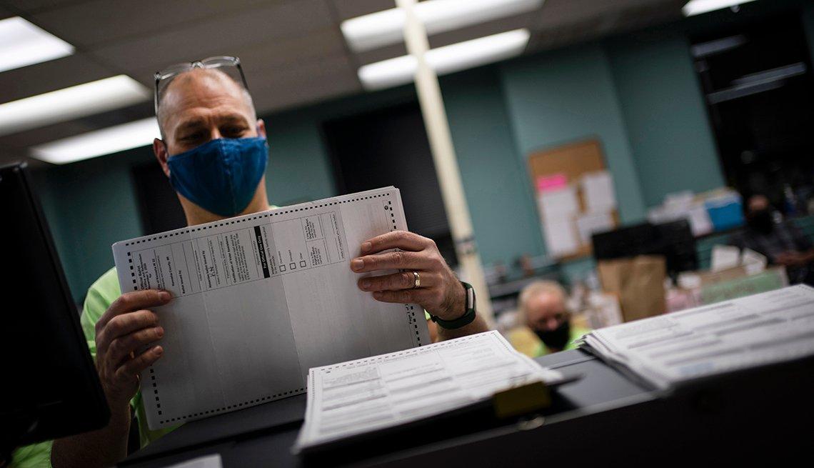 Funcionario electoral clasifica papeletas de votación anticipada